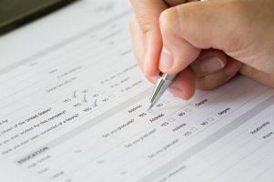 mao-com-a-pena-sobre-caixas-de-selecao-em-branco-no-formulario-de-candidatura_1232-1700