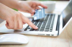 mao-com-um-cartao-de-credito-e-um-computador-portatil_1232-619